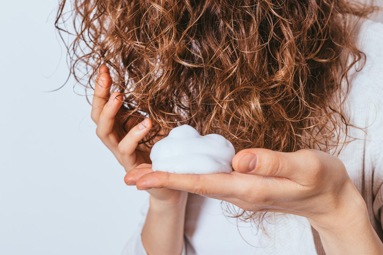 espuma na mão de mulher com os cabelos encaracolados