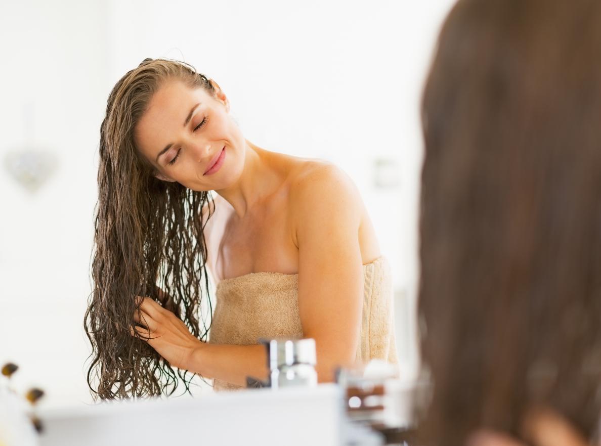 mulher secando os cabelos após terminar o seu banho