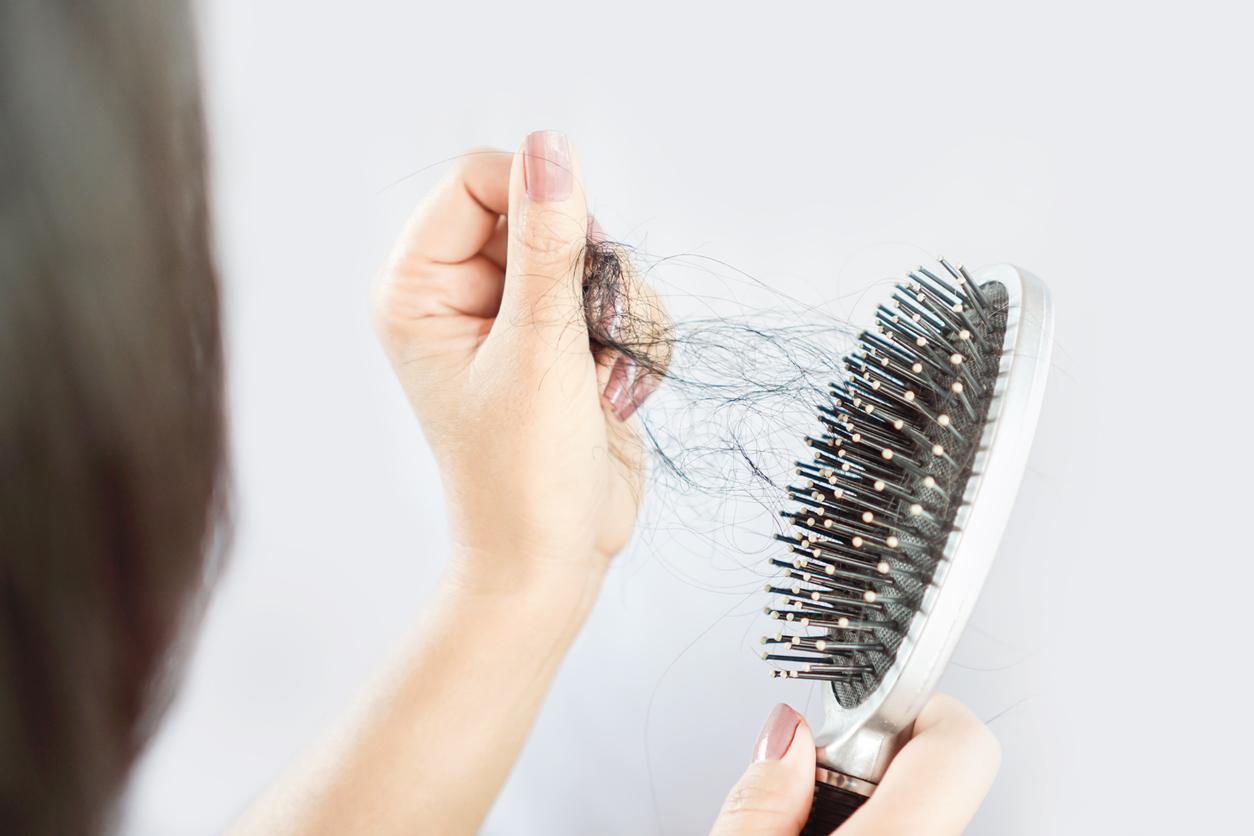 mulher retirando cabelos da escova de cabelo