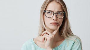 mulher loira de óculos pensativa