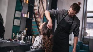 cabelereiro com as mãos no cabelo da cliente