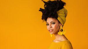 mulher negra sorrindo com fundo amarelo