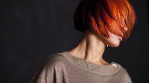 mulher ruiva de cabelo curto com os cabelos sobre o rosto