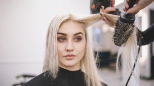 mulher loira sentada no salão de beleza tendo os cabelos escovados
