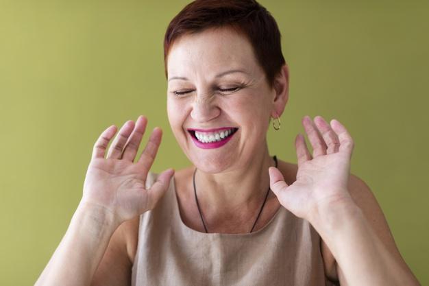mulher de brinco sorrindo com as mãos para cima