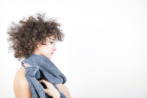 mulher com frizz nos cabelos com toalha