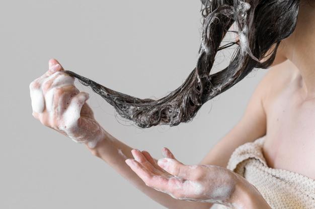 mulher segurando os cabelos ensaboados