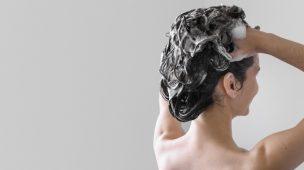 mulher de costas ensaboando os cabelos
