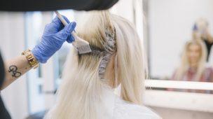 cabelereiro aplicando tinta na raiz de cabelo da cliente loira