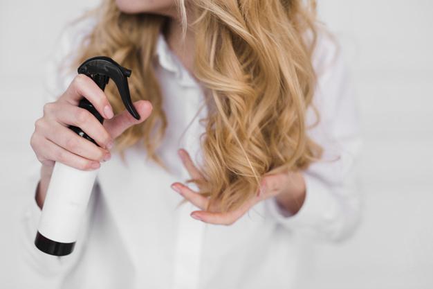 loira de branco borrifando os cabelos