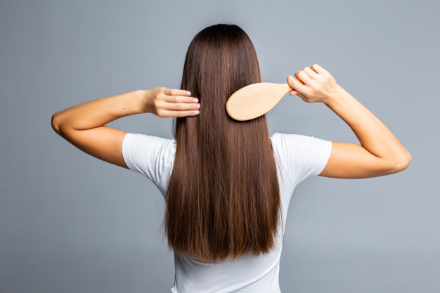mulher de costas penteando os cabelos