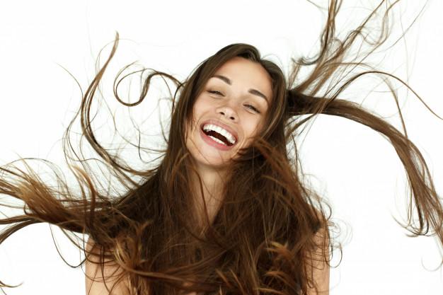 mulher sorrindo com os cabelos voando