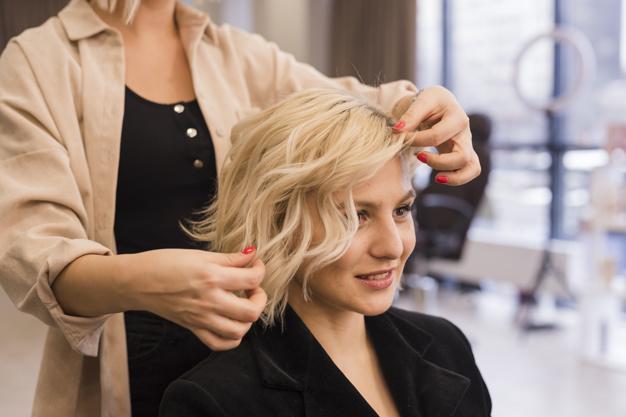 mulher loira sentada no cabelereiro