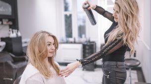 cabelereira passando spray no cabelo de cliente loira sentada no salao