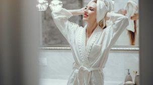 mulher sorrindo de roupao com toalha na cabeça