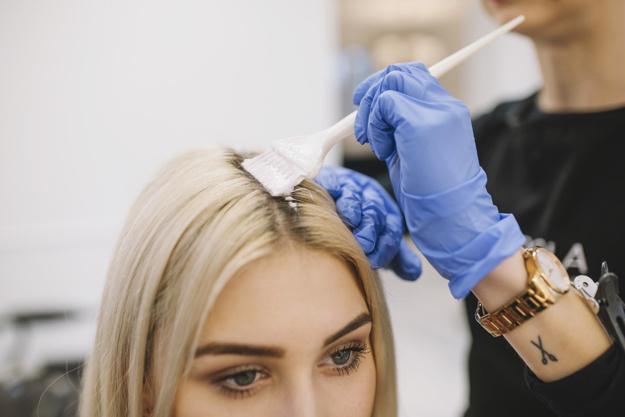 cabelereira pintando o cabelo de cliente loira