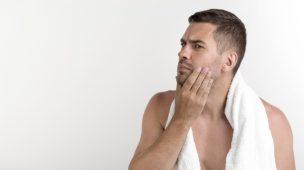 homem com toalha no pescoço passando mão na barba