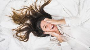 mulher com os cabelos soltos deitada sorrindo