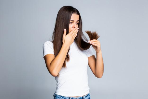 mulher com mão na boca segurando o cabelo