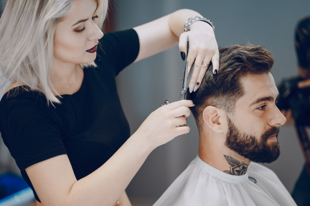 cabelereira cortando o cabelo de cliente homem