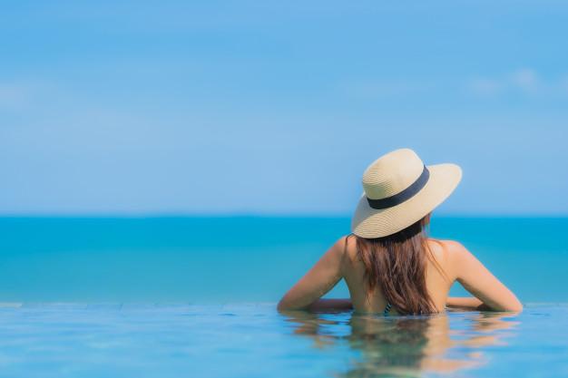 mulher de costas de chapéu na piscina