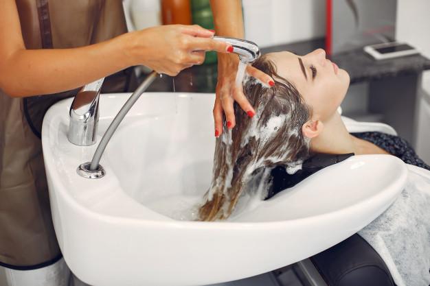 cabelereira lavando cabelo de cliente