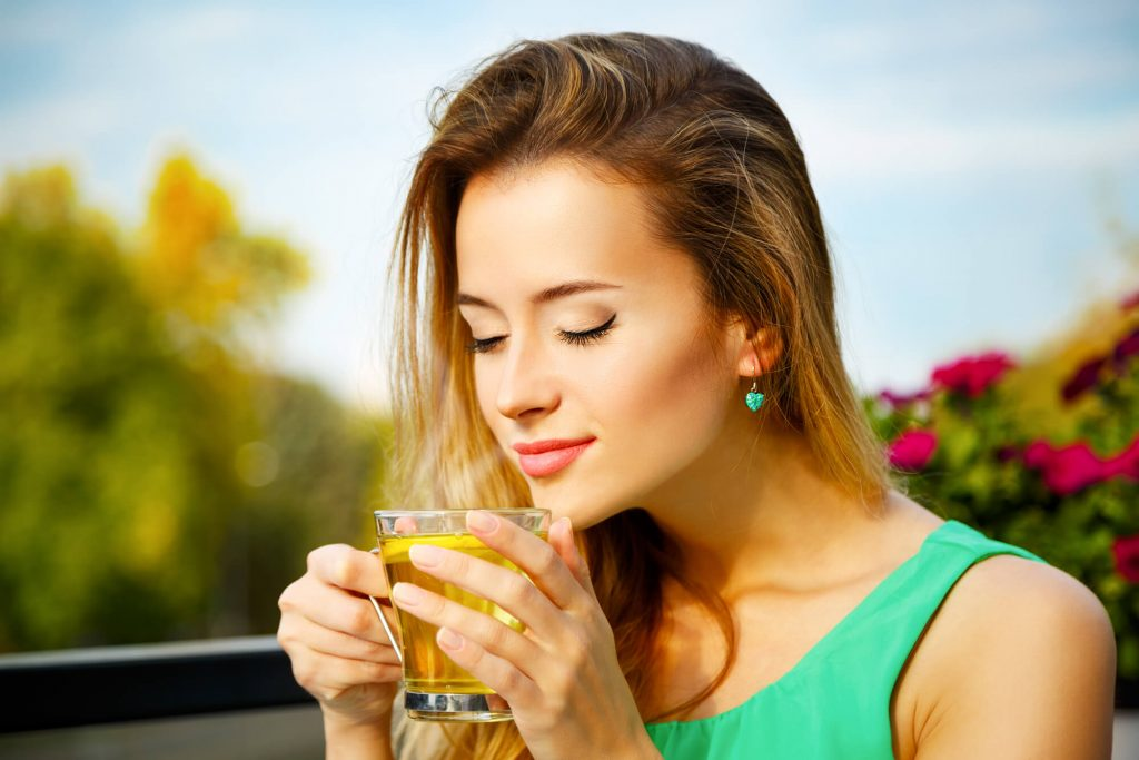 mulher loira com os olhos fechados apreciando chá