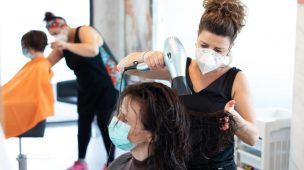 cabelereira de mascara usando o secador de cabelo na cliente-sentada