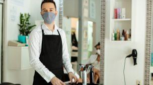 cabelereiro de mascara no salão de beleza segurando pente nas mãos