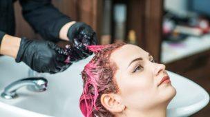 mulher sentada com os cabelos sendo pitados de rosa