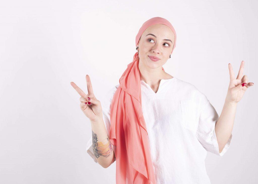 mulher com câncer com lenço rosa sobre a cabeça