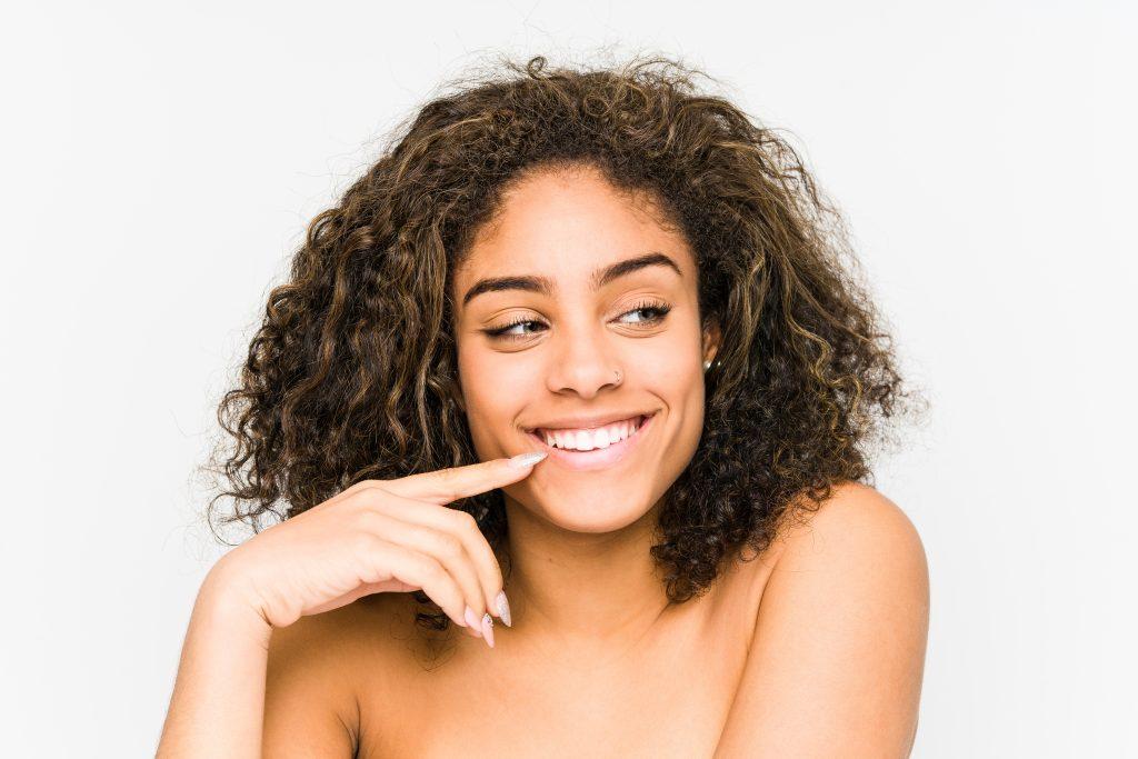 mulher negra feliz dia depois de realizar transição capilar
