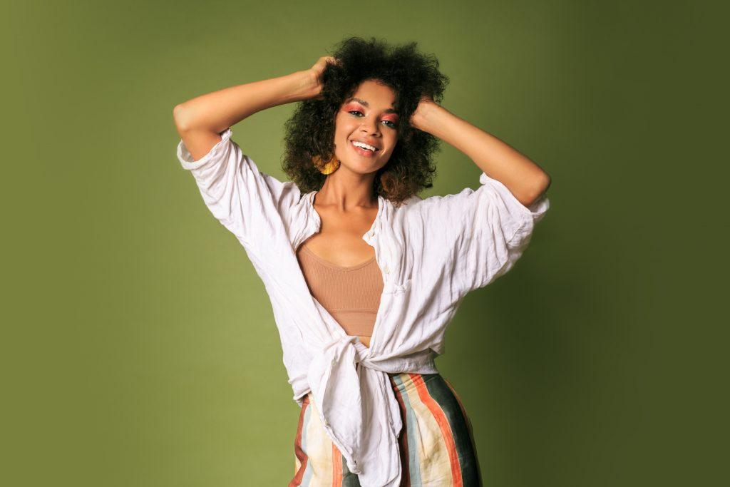 mulher negra feliz com cabelos com frizz