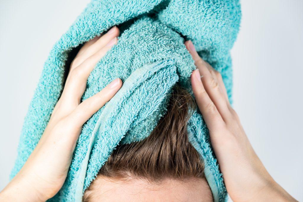 mulher secando os cabelos com toalha de algodão