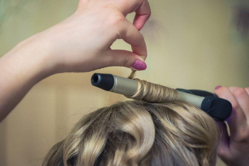 Foto em close, mãos fazendo a ondulação no cabelo, com um babyliss