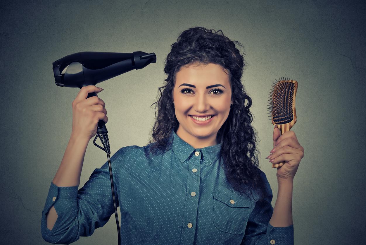Mulher com cabelos ondulados, segura o secador de cabelo e a escova, para fazer seu penteado