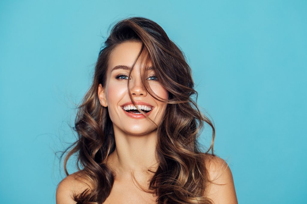Mulher de cabelo castanho escuro, liso, sedoso e hidratado, sorrindo, mostra o resultado do tratamento para cabelos ressecados