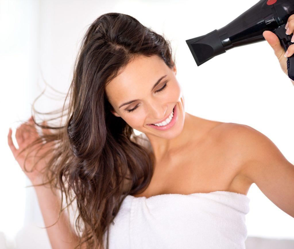 Mulher, de toalha, sorri enquanto seca o cabelo para fazer seu penteado