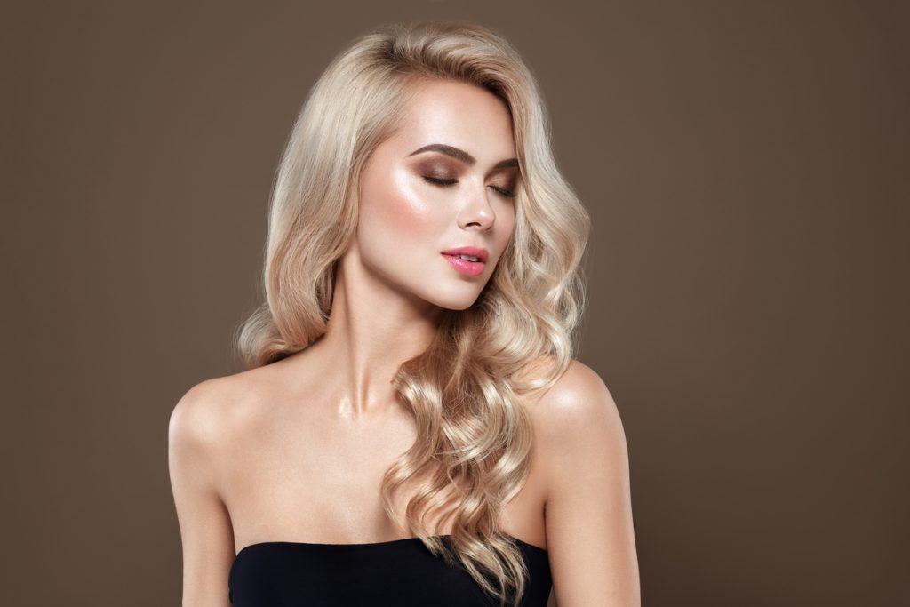 Mulher loira com o cabelo sedoso e hidratado, de olhos fechados e rosto de lado, mostra o resultado do tratamento para cabelos ressecados