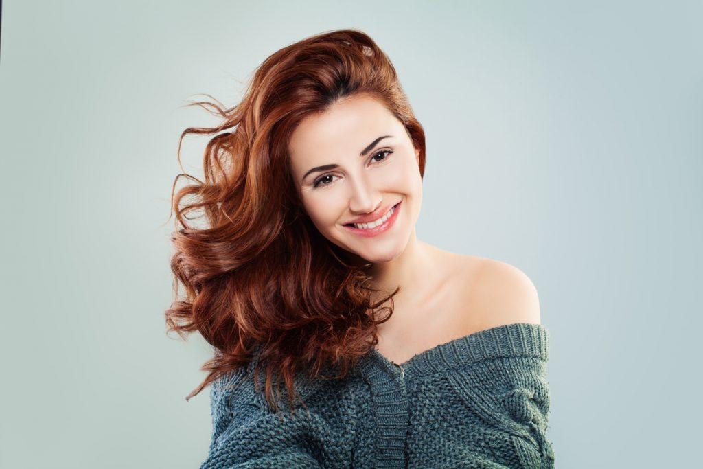 Mulher ruiva, com o cabelo sedoso e hidratado, sorrindo, mostra o resultado do tratamento para cabelos ressecados