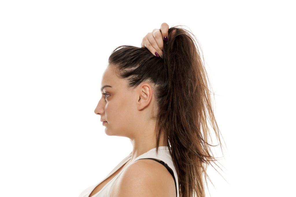 Mulher se posiciona de lado e segura o cabelo, fazendo um rabo de cavalo, com uma das mãos, para fazer o seu penteado.