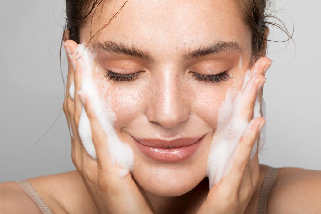 Uma mulher branca, de olhos fechados, passa uma espuma branca com as duas mãos no rosto